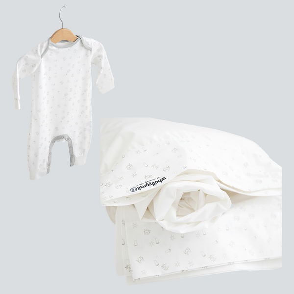 Image shows products in the baby sleep bundle. Your choice of long, organic cotton onesie and organic cotton cot sheets in white with printed detail in dove grey.