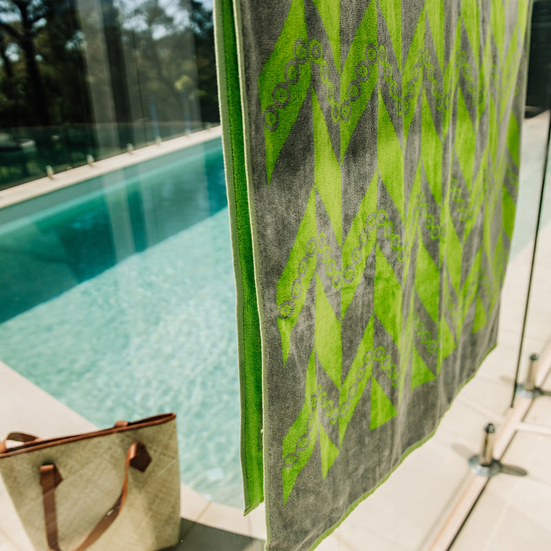 Close up of green and grey towel over glass fencing around a pool with bag beside.