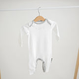 Long Onesie in super soft organic white cotton with chest print and piping in dove grey. Hanging on rack