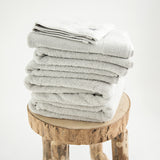 Organic 7 Piece Towel Set, in 700GSM cotton, stone colour, folded on stool. 2 bath towels, 2 hand towels, 2 face towels, 1 bath mat.