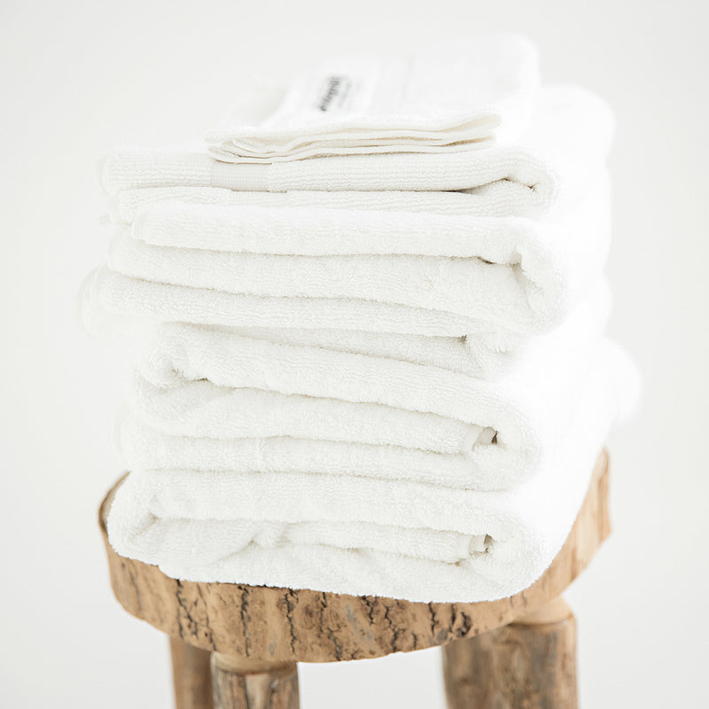 Organic 7 Piece Towel Set, in 700GSM white cotton, folded on stool. 2 bath towels, 2 hand towels, 2 face towels, 1 bath mat.
