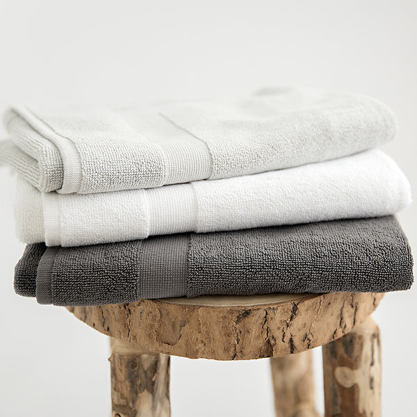 Organic cotton bath mats in stone, white and charcoal, folded on stool.