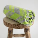 Organic beach towel rolled up on stool. Herringbone print in green and grey.