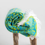 Organic mandala towel, 130cm round. Green and blue with white tassel. Rolled on stool