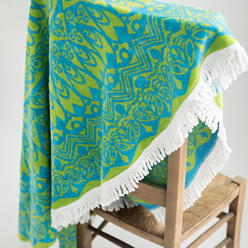 Organic mandala towel, round 130cm draped across back of chair. Green and blue with white tassel
