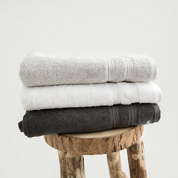 Organic bath towels in 700GSM GOTS cotton. Pictured in stone, white and charcoal.