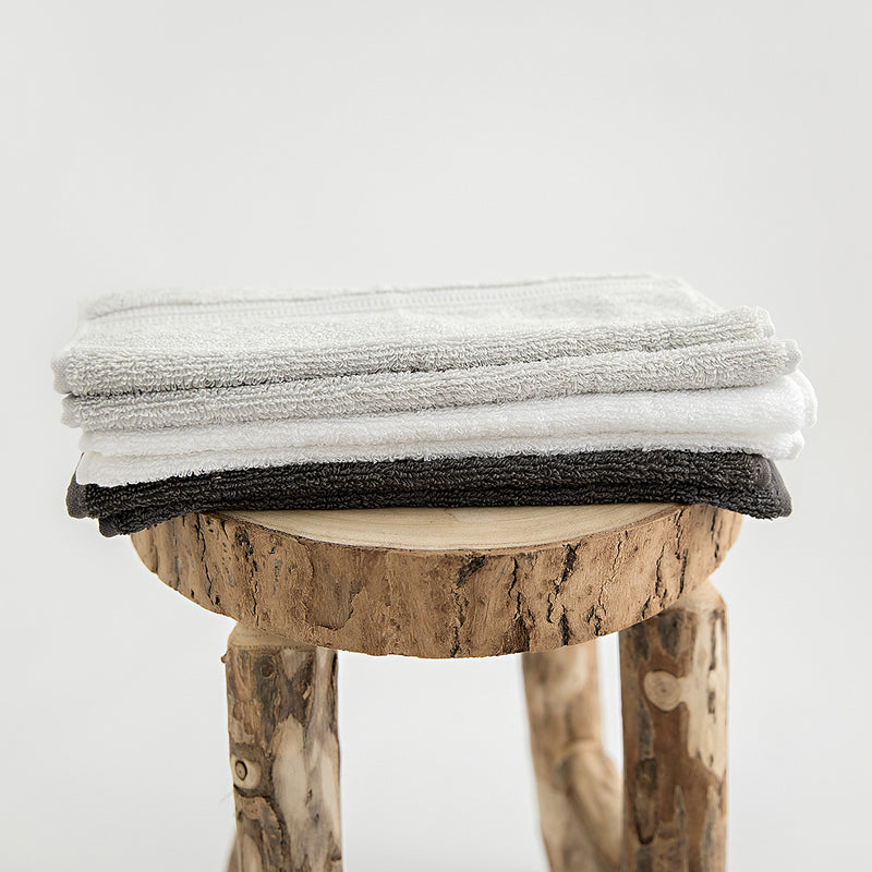 Organic cotton face towels folded on stool. Stone, white and charcoal.
