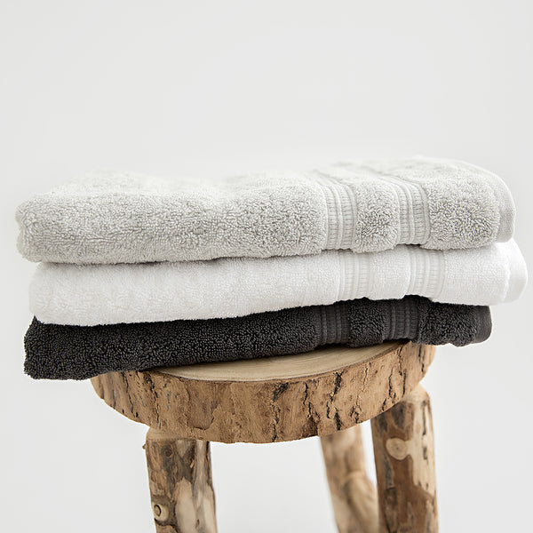 Set of 3 hand towels folded on stool. Stone, white and charcoal