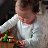 Baby wearing long green organic cotton onesie playing with wooden toys on a wooden stool.