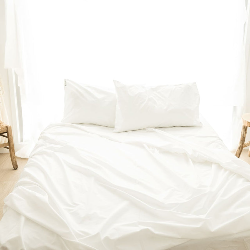 View from above of organic white sheet set on a bed with two pillows and ruffled sheets, backlit with white curtained window and wooden stools either side of bed.