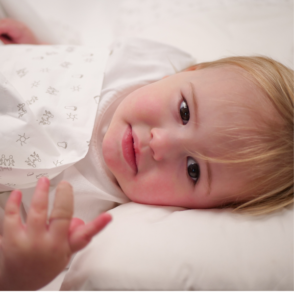 Image of toddler in organic cot sheets.