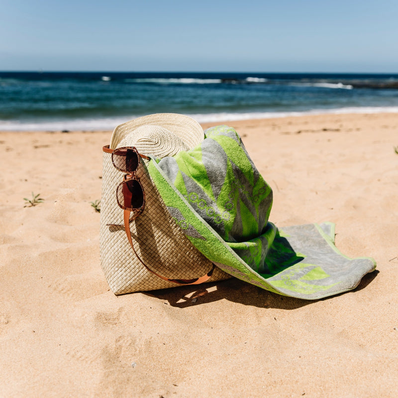 Green and grey herringbone towel spilling out of a bag with sunglasses and hat at the beach with waves in the background