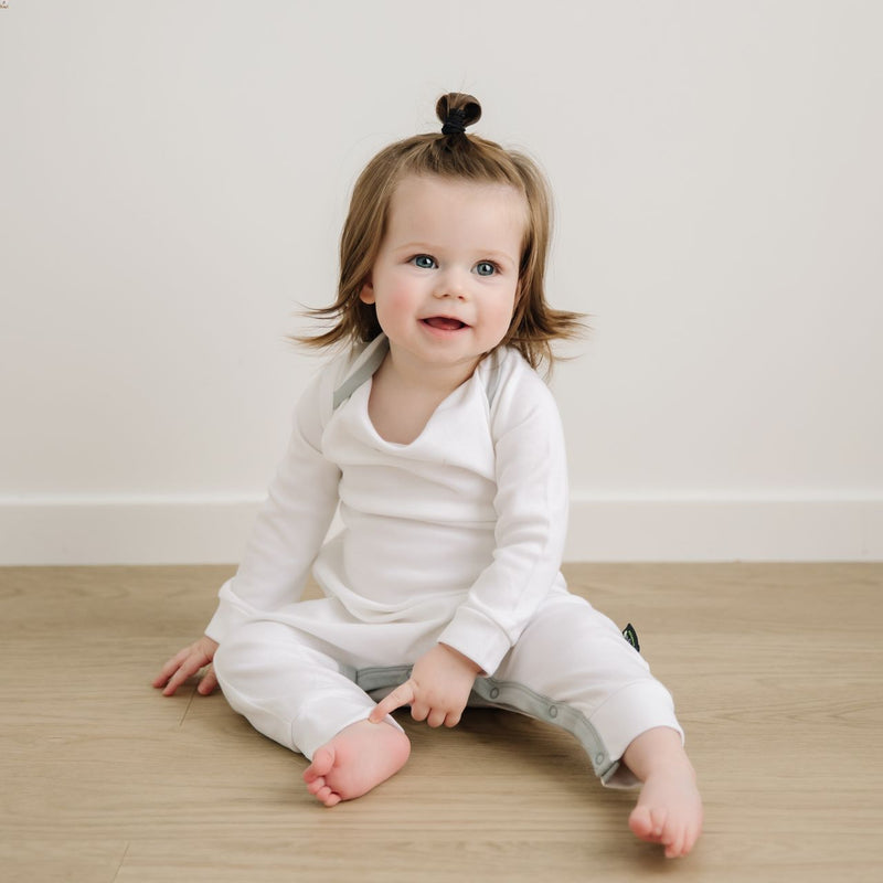 Toddler sitting on floor in long white organic cotton onesie