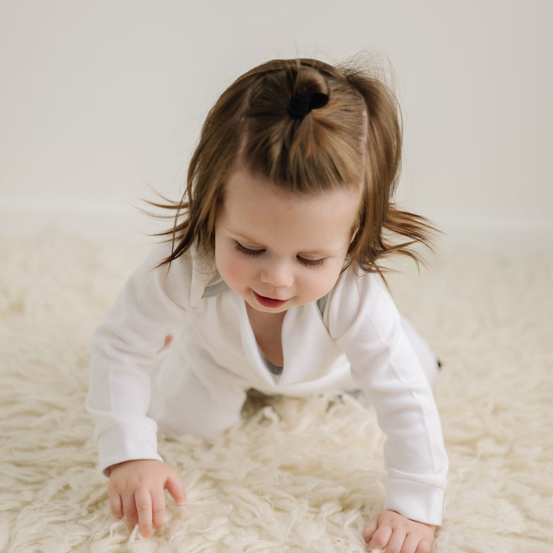 Toddler crawling on woollen rug in long white organic cotton onesie