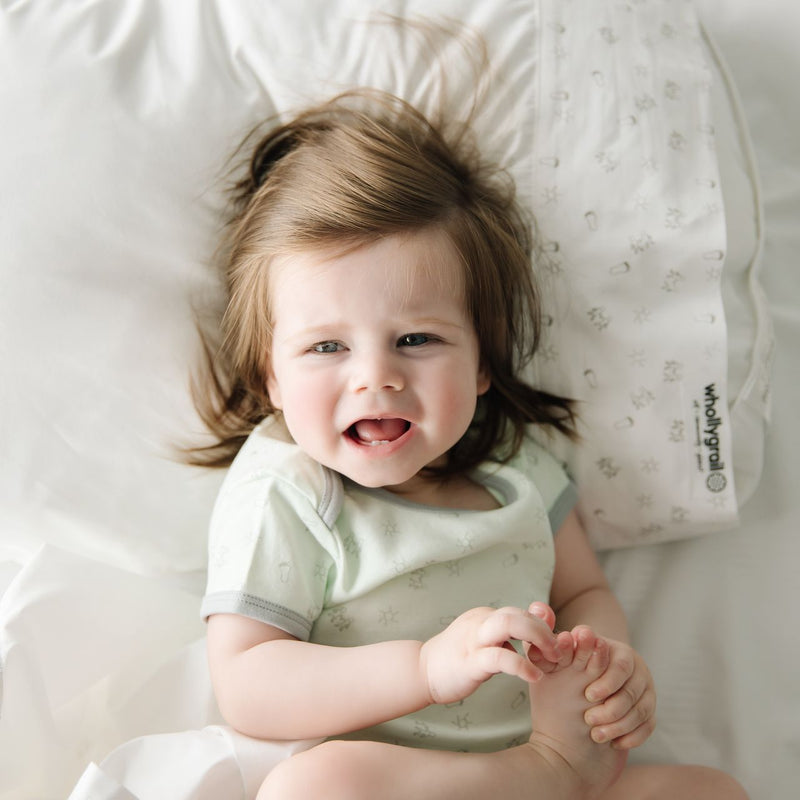 Baby smiling and holding feet in green onesie lying on cot sheets and pillow.