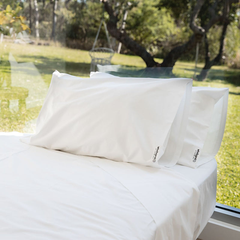 Organic cotton sheet set in white on bed with two pillows against a window with grass, swing and trees in background