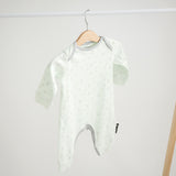 Long Onesie in super soft organic cotton, light green with dove grey print and piping. Hanging on rack.