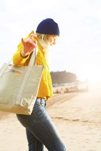 Woman Walking on Beach on Cold Day wearing Yellow Jacket Design Go