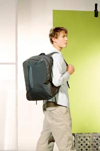 Young man walking through airport with backpack Design Go