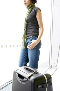 Woman waiting at airport looking out window at planes with luggage nearby