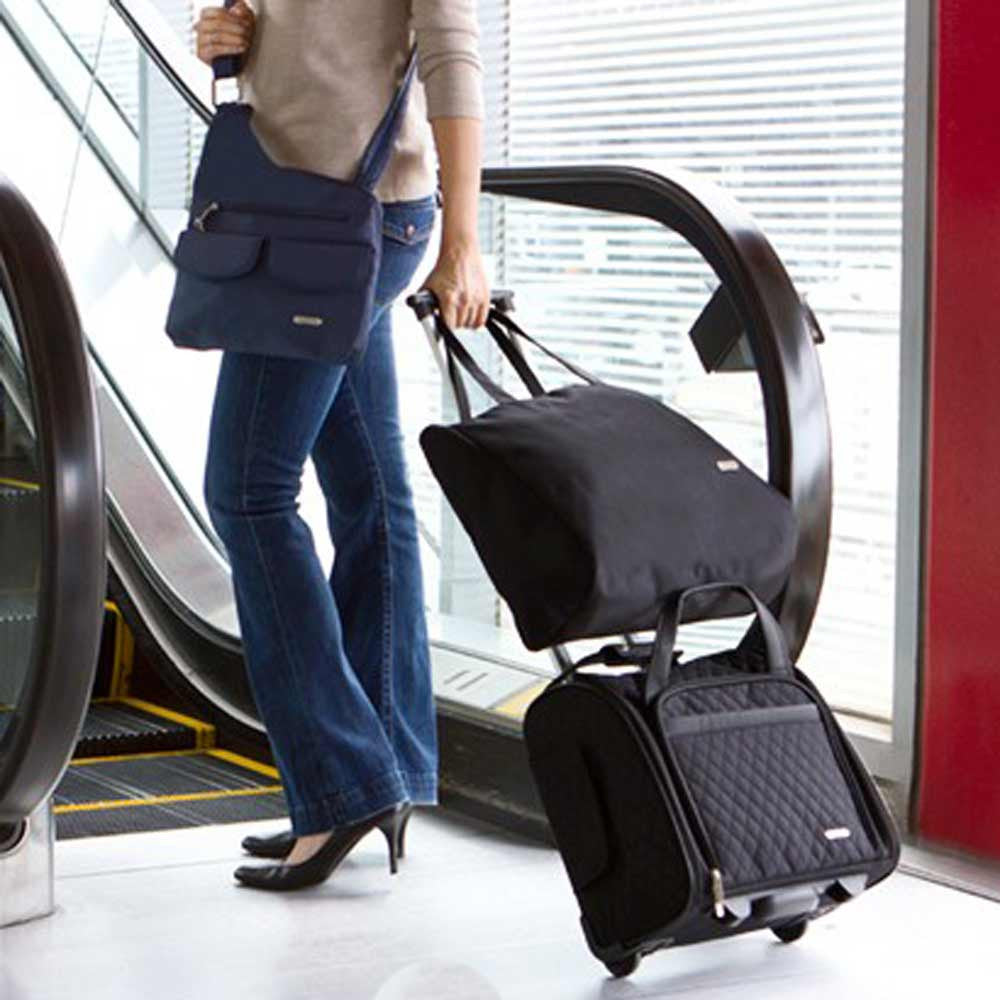 4b0b16760eba ... bag for overflow luggage and bringing back souveniors · Woman rolling  her Travelon Wheeled Underseat Carry on through airport ...