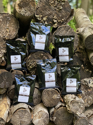 Bags of coffee that are laid across a wood pile.