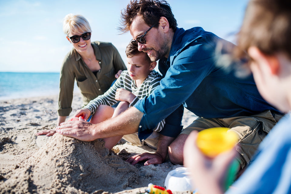 family with kids ages 8 to 10 building a sand castle