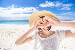 asian woman at the beach holding up her hands in the shape of a heart