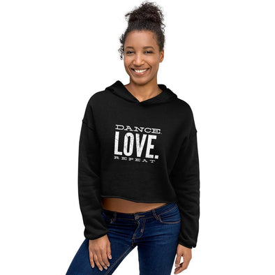 smiling woman wearing a black crop hoodie and jeans
