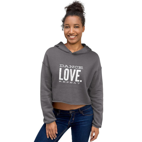 smiling woman wearing a grey crop hoodie and jeans