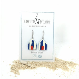 Abstract beach huts drop earrings with vertical rich blue and white strips, white roof and red doors. The earrings hang from a Harriett & Evelynn branded card. The card has a small amouont of white pebbly sand around it.