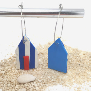Abstract beach hut earrings hanging from silver coloured hoops. The beach hut on the left has vertical rich blue and white stripes and a red door. The beach hut on the right shows the back of the design with a plain sky blue back. The earrings are gently sitting on white pebbly sand.
