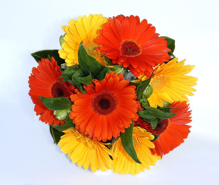 Orange and yellow gerberas with greenery