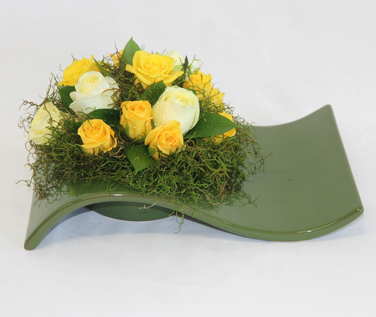 Yellow shades of roses nestled in moss.  - One green ceramic dish.