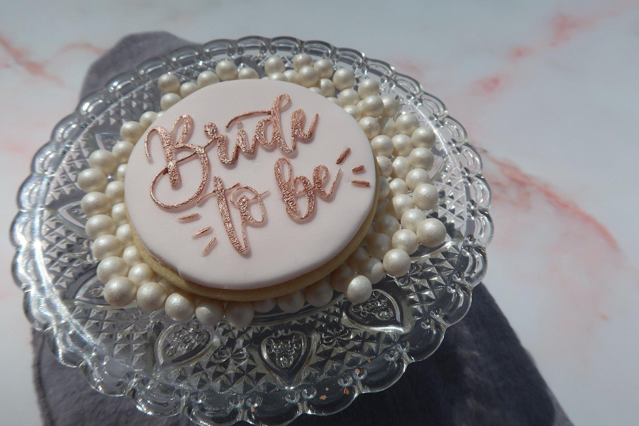 Bride to Be cookie sitting on pearls in a glass dish