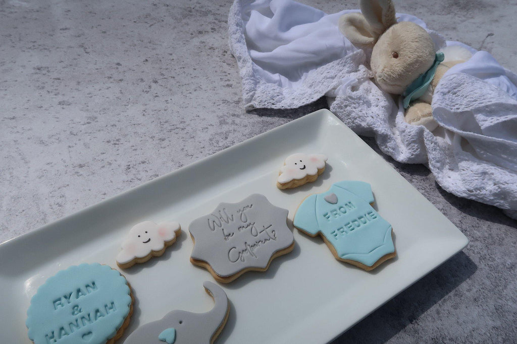 Godparent proposal cookie set, blues and greys, ryan and hannah from freddie, baby vest cookie, grey elephant cookie, white clouds cookie.  Sitting on white plate beside a toy bunny