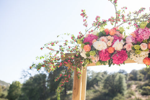 Arch arrangement with blossoms, green hydrangea, roses and peonies.