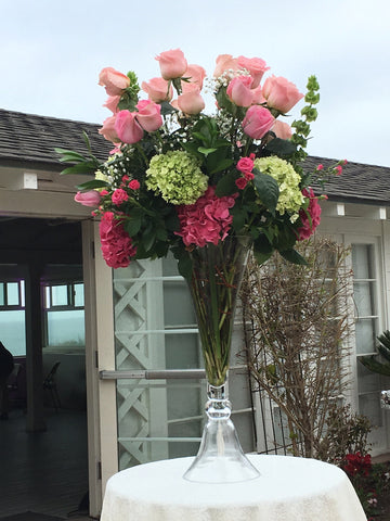 Pink and green hydrangea along with tall pink roses and bells of ireland as the final touch.