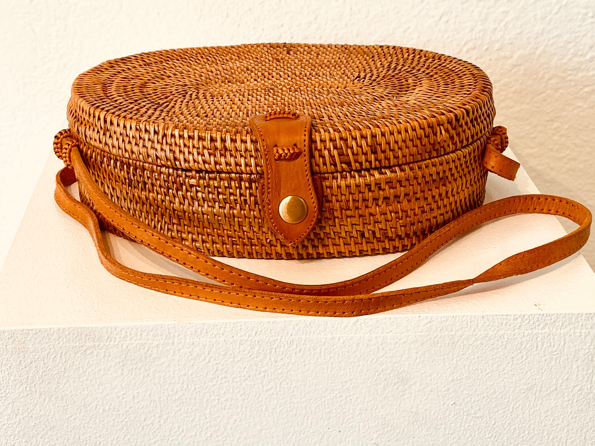 This over the shoulder purse made in Bali has a lovely circular design, a button snap for tight closure with a lining of cool greens, purples and pinks.