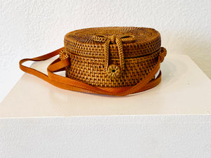 This is a little gem of a woven purse hailing from Bali has an adorable bow closure and a golden, green and maroon lining.
