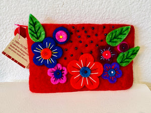 This small purse was made by hand in Nepal with fair trade. Its brilliant floral design makes it a unique piece.