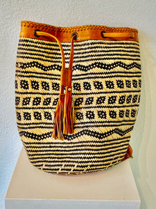 This spacious beautifully woven backpack from Bali has a tribal design: cream colored interspersed with black and has an adjustable closure with tassels and leather back straps. The backpack can easily hold a laptop with lots of room to spare!