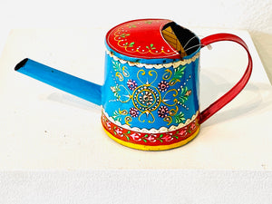 This beautifully decorated watering can will brighten up any little corner with its vibrant colors and cool blue.  Hand-crafted in India this product is fair trade, sustainable and funds community development. The metal engraving is a 500 year old tradition by the Rajput Kings of West India.