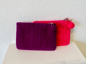 This pouch was designed and made in Nepal through fair trade. You will love its textured surface and quality lining with an adorable pompom. The colors are hot pink and purple.