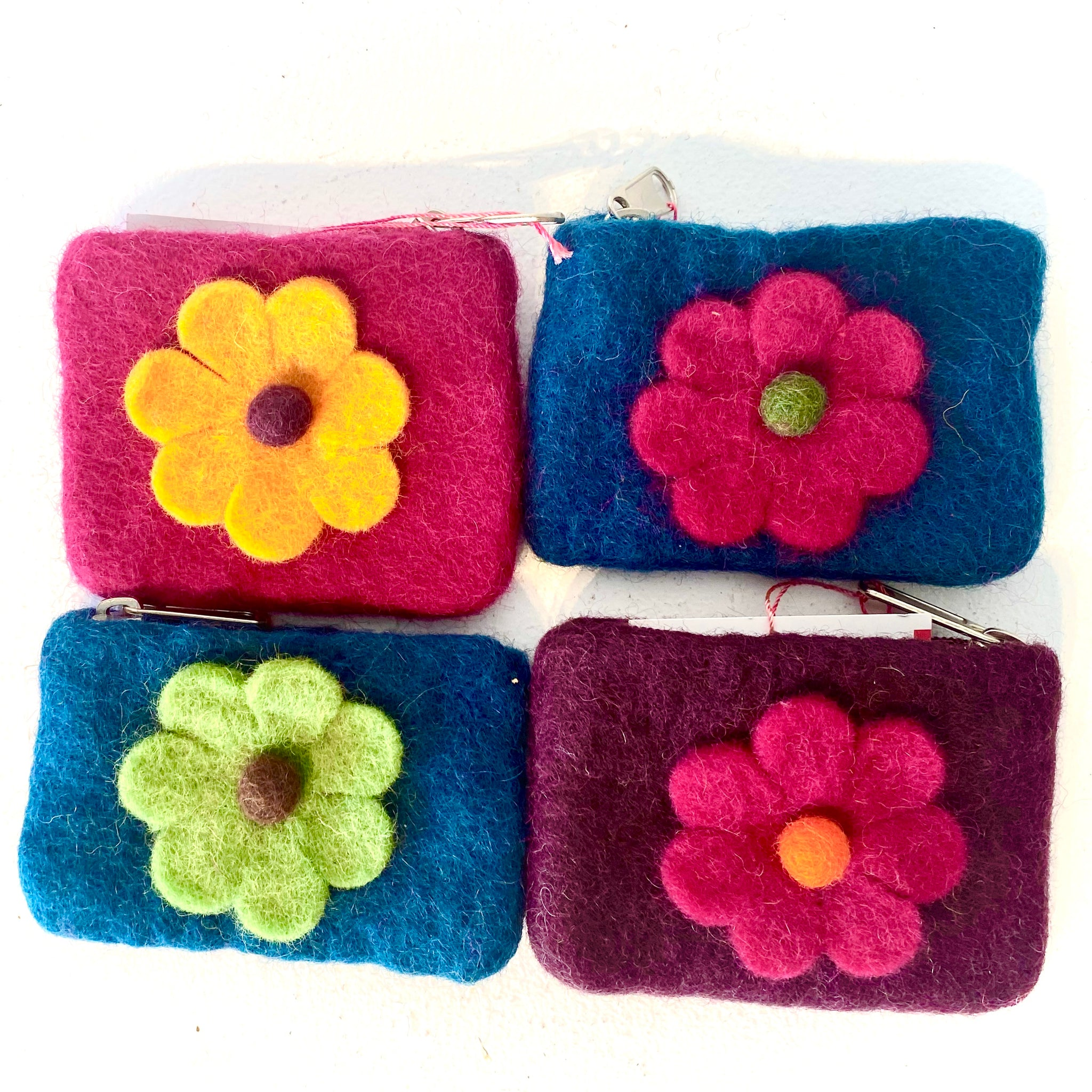 This adorable coin purse was designed and made in Nepal through fair trade. You will love its textured surface and quality lining with an adorable little flower on the front. The colors are: red with yellow flower, blue with pink flower, blue with green flower, and purple with pink flower.