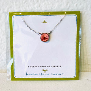 Noon designs brings you a beautiful handmade in America necklace, understated yet with a bright, sparkling stone. Available in four colors: salmon, pink, blue and crystal.