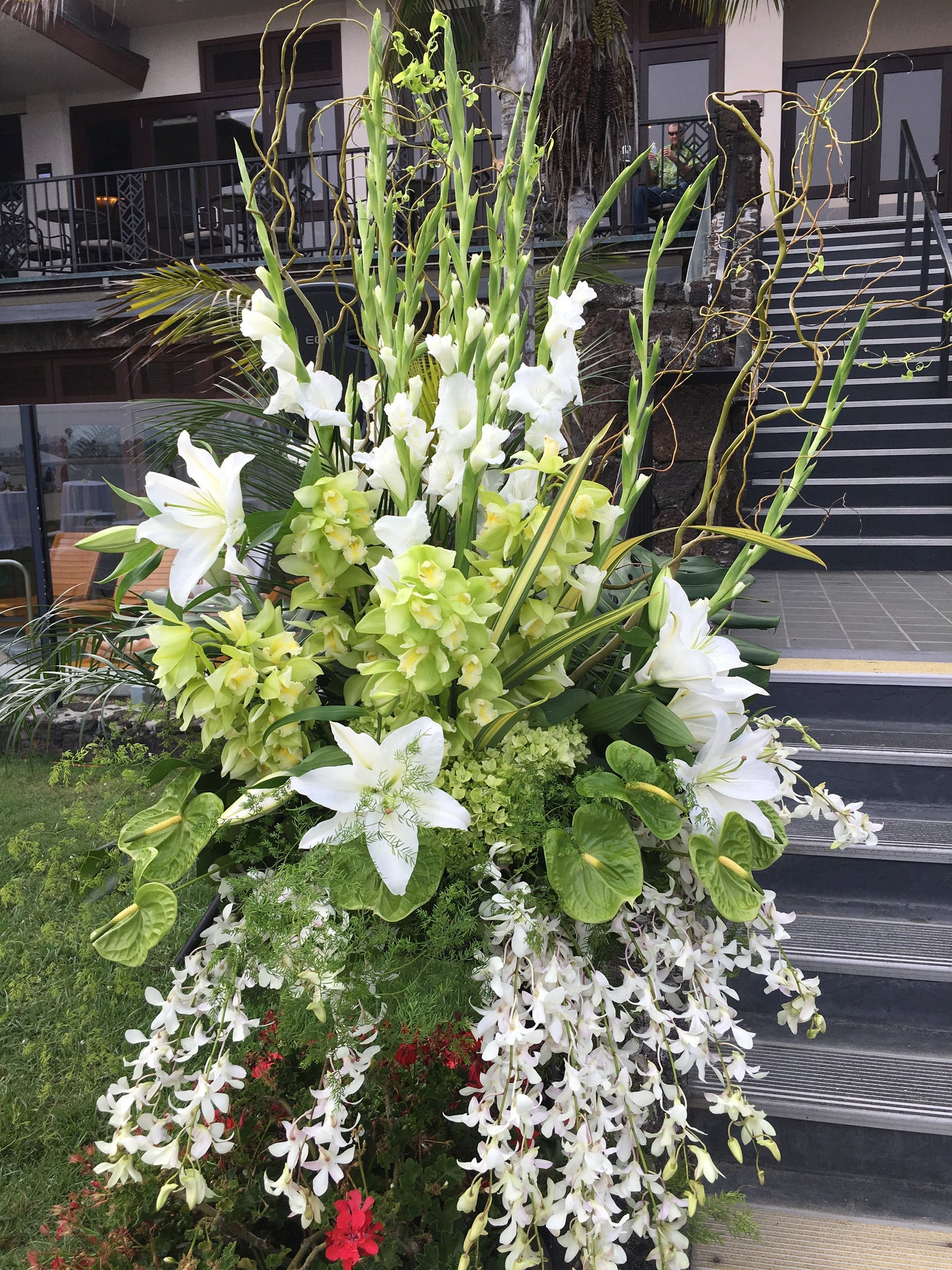 This gorgeous wedding entrance piece consists of white gladiolas high and to the back with green Cymbidium orchids and white Casablanca lilies towards the middle, green Anthurium towards the bottom and lovely white orchids cascading towards the bottom, a beautiful statement piece.