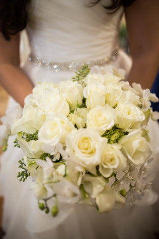 The gorgeous white bouquet includes white roes along with white orchids accompanied by seeded eucalyptus.