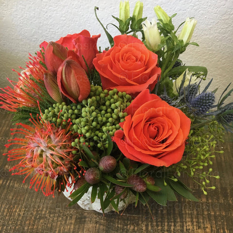 This bright display of flowers contains orange Protea pin cushions, bright orange roses along with seeded eucalyptus.