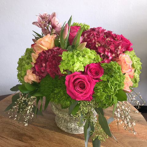 This gorgeous floral design has pink and green hydrangea along with pink and light orange roses with stems of Genestra cascading down.  Perfect for a table centerpiece or a quiet corner in the house, this design fits anywhere.